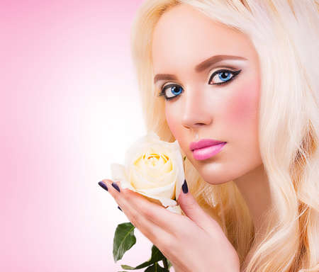 Beautiful blonde girl with white rose photo