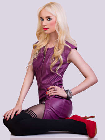 Beautiful fashionable blonde girl in dress on greay background photo