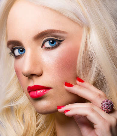 Beautiful blonde model with red lips and manicure photo