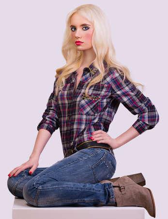 Beautiful fashionable girl posing on grey background