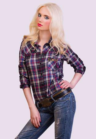 Beautiful blonde girl posing on grey background photo