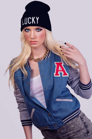Beautiful fashionable blonde model posing on grey background