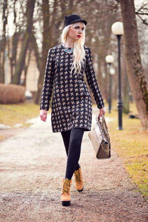 Beautiful blonde young woman walking on the street photo