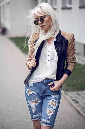 Beautiful blonde woman in posing outdoors