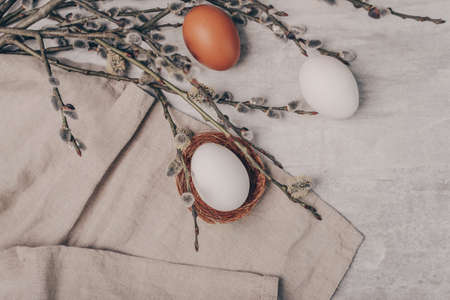 Easter eggs and willow branches on grey background