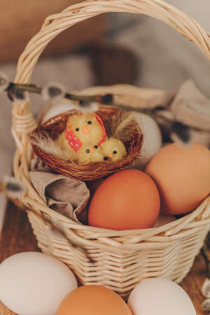 Easter eggs with little chick toys in basket.