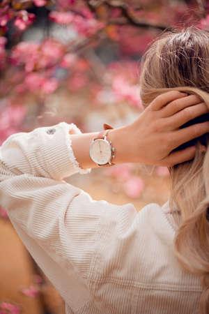 Stylish white watch on woman hand in flowers 版權商用圖片