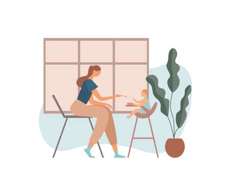 Mother feeding baby in kitchen. Woman in casual clothes giving food to baby sitting on feeding chair near potted plant and window during lunch in cozy kitchen at home