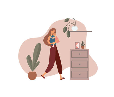 Woman hugging baby at home. Loving mother in casual clothes carrying and embracing little baby while walking near cabinet with decorations and potted plants in cozy room at home