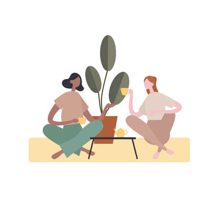 Diverse women drinking tea and talking at home. Multiracial female friends enjoying fresh tea and speaking with each other while sitting crossed legged near table and potted plant in cozy home