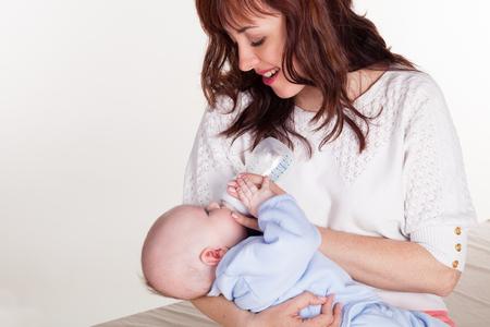 feeds: mom feeds the baby newborn little bottle