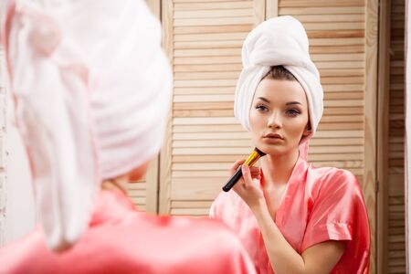 make up face: girl in the Spa doing makeup in front of the mirror