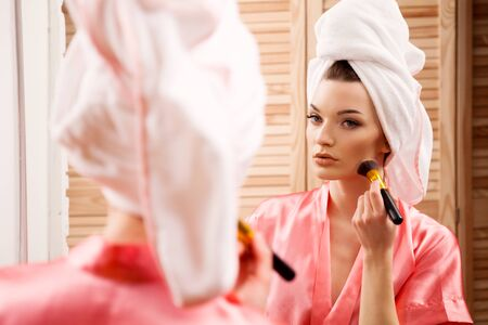 dark complexion: girl in the Spa doing makeup in front of the mirror