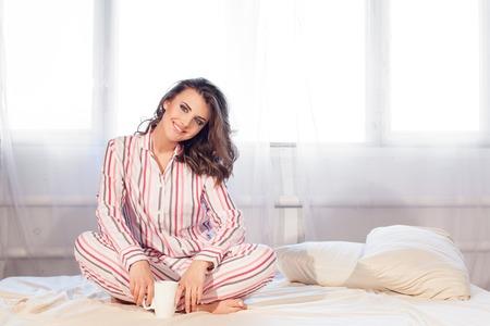niña en pijama se despertó por la mañana en la ventana Foto de archivo