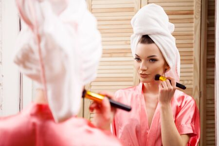 dark complexion: the girl from the Spa is painted in front of the mirror Stock Photo