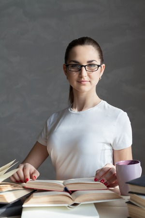 erudition: girl with a mug is preparing for the exam reading the Carnet Stock Photo