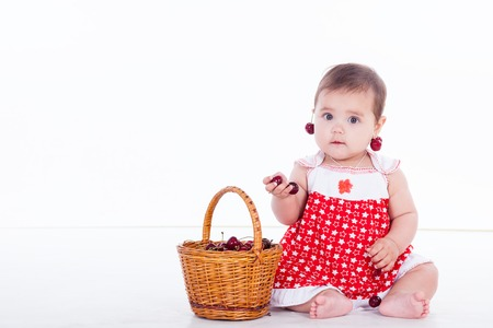 little girl with a basket of eating cherries