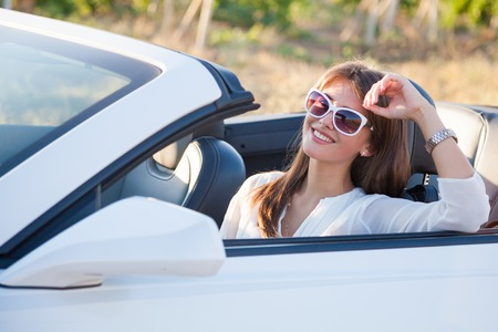 the girl sitting behind the wheel of a white sports convertible 스톡 콘텐츠