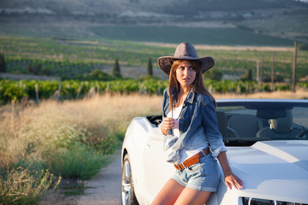 hot teenage girl: Cowboy girl standing next to a white cabriolet