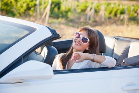 summer sport: beautiful girl driver sits in white cabriolet