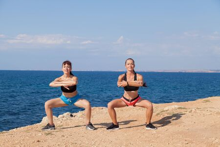 beautiful girls engaged in fitness squat , beach