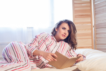 girl in pajamas lying on the bed and reading