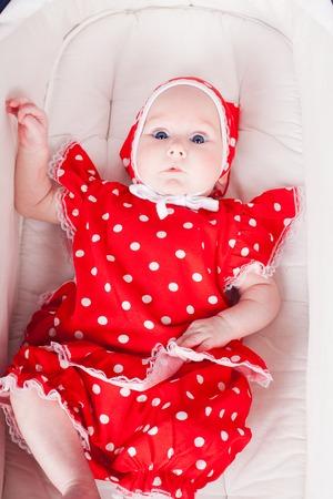 pezones: Niña en un cochecito de vestido rojo Foto de archivo