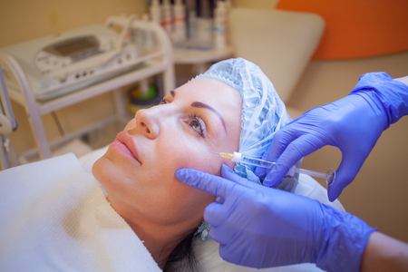 doctor beautician increases lip patient an injection syringe Spa