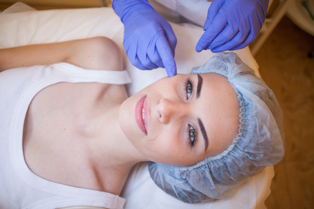 popular: doctor cosmetologist shows on face patient Spa Stock Photo