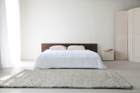 wooden floors: White bedroom bright interiors with bed and flowers Stock Photo