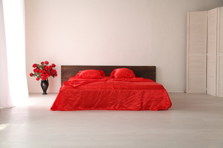 lodgings: the Interior of the white room with a bed with red