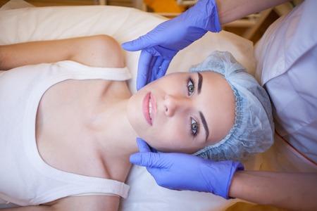 Cosmetologie arts maakt vrouw behandelingen gezichtsmassage