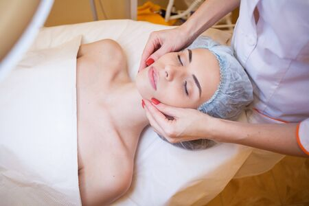 Cosmetology doctor makes woman treatments facial massage Stock Photo