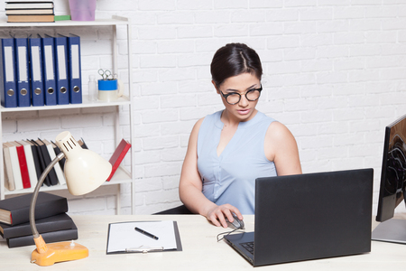 hectic: business girl sits in an Office behind a desk with a computer