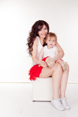 mother and little daughter in red skirts on a white background Zdjęcie Seryjne