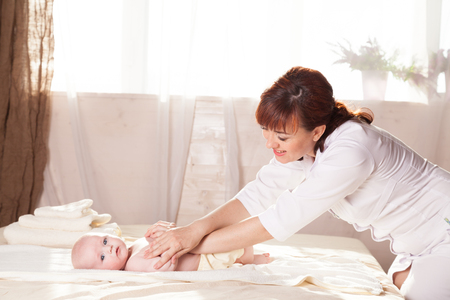 the little boy baby mother doing massage hands and legs Stock Photo