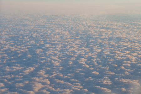 flying above the clouds at sunset landscape from an airplane 1