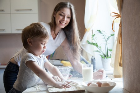kiss biscuits: mother and young son prepare a cake in the kitchen