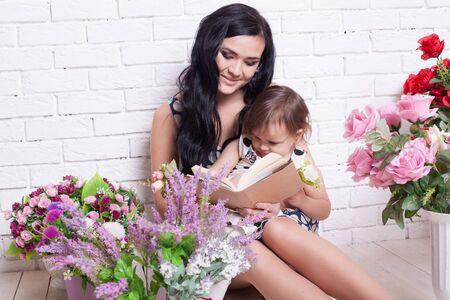 niños reciclando: mother and daughter read the book flowers family Foto de archivo
