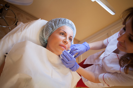 doctor beautician increases lip patient an injection syringe Stock Photo