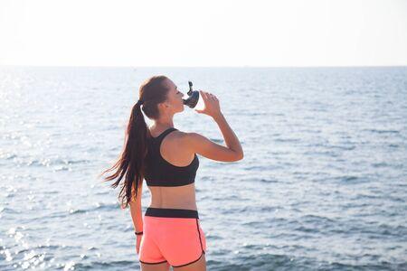 Mädchen trinkt Wasser aus einem Mixer nach dem Sport Standard-Bild