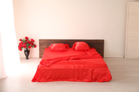 home decorating: the Interior of the white room with a bed with red