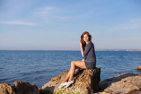 the girl in the striped dress sits on the rocks by the sea