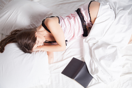 girl in pajamas lying on the bed with a book before bed