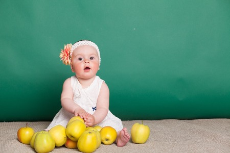 baby girl in a dress with Green apples Stock Photo