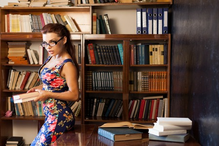 femme bibliothécaire dans des verres assis à la table livre d & # 39 ; étude