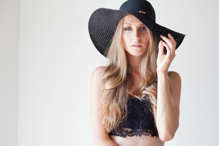 fashionable girl in a hat with a brim poses for advertising