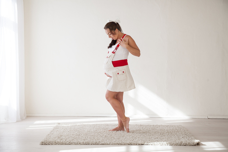 pregnant woman posing in a white room