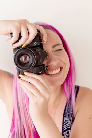 photographer girl with pink hair on a photo shoot with a camera Stock Photo