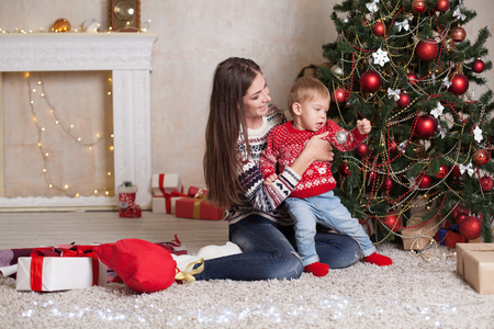 mom with son decorate tree on new years Gifts Christmas